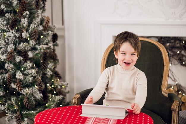 Porträt des netten kinderjungen, der auf grünem stuhl sitzt und mit computertablette während der weihnachtszeit spielt. ferienzeiten.