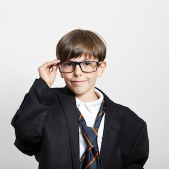 Porträt des netten kindes aufwerfend als geschäftsmann