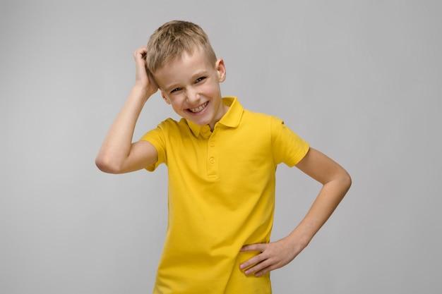 Porträt des netten kleinen blonden kaukasischen jungen im gelben t-shirt denkend auf grau