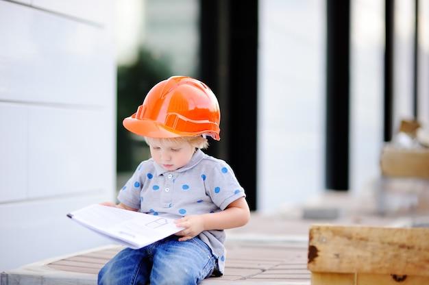 Porträt des netten kleinen erbauers in den hardhats bauzeichnung draußen lesend