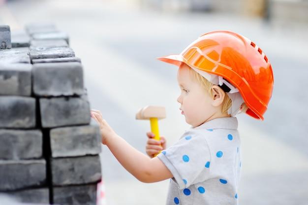 Porträt des netten kleinen erbauers in den hardhats mit dem hammer, der draußen arbeitet
