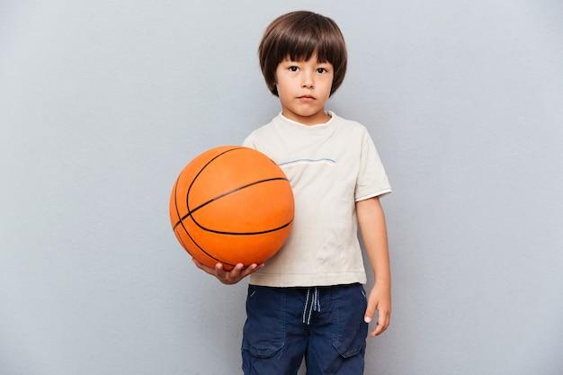 Porträt des netten kleinen jungen, der basketballball steht und hält