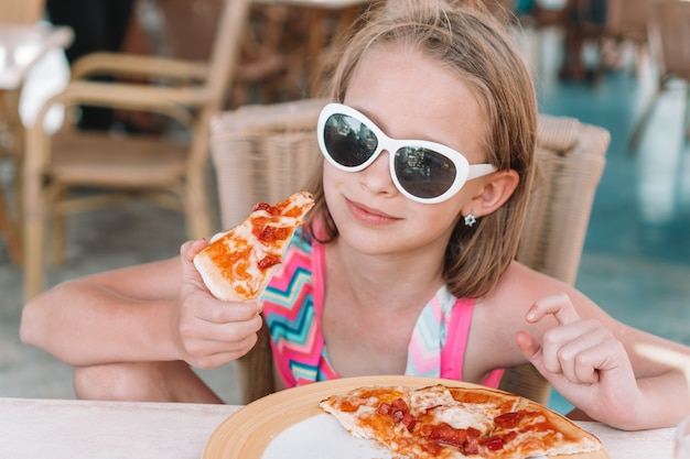 Porträt des netten kleinen mädchens, das durch abendtische sitzt und pizza isst