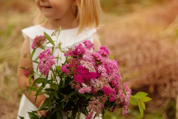 Porträt des netten kleinen mädchens das händchenhaltenblumenstrauß von rosa blumen auf einem feld
