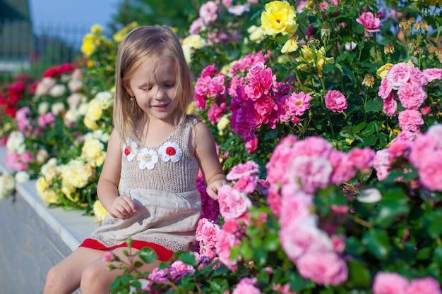 Porträt des netten kleinen mädchens nahe den blumen im yard ihres hauses