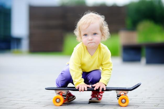 Porträt des netten kleinkindmädchens mit skateboard draußen