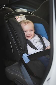 Porträt des netten lächelnden babys, das im autokindersitz sitzt