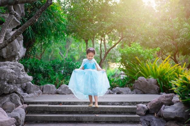 Porträt des netten lächelnden kleinen mädchens in prinzessinkostüm gehend hinunter die treppe im park