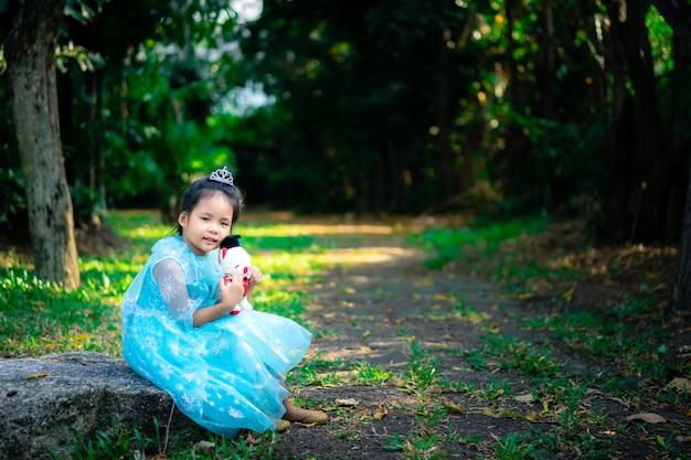 Porträt des netten lächelnden kleinen mädchens in prinzessinkostüm mit der puppe, die auf dem felsen im park sitzt
