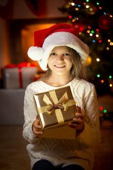 Porträt des netten lächelnden mädchens, das gegen kamin und weihnachtsbaum mit geschenkbox aufwirft