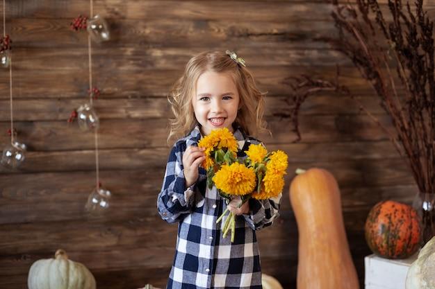 Porträt des netten lächelnden mädchens mit blumenstrauß von gelben blumen