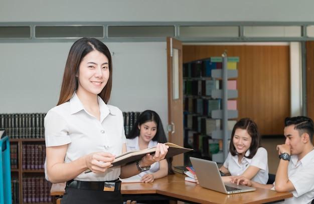 Porträt des netten lächelnden studentenlesebuches mit einer gruppe studenten, die an der bibliothek, educa arbeiten