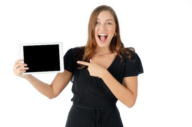 Porträt des netten lächelns der recht jungen kaukasischen frau und des haltens der schwarzen tablette des leeren bildschirms im schwarzen kleidungskleid