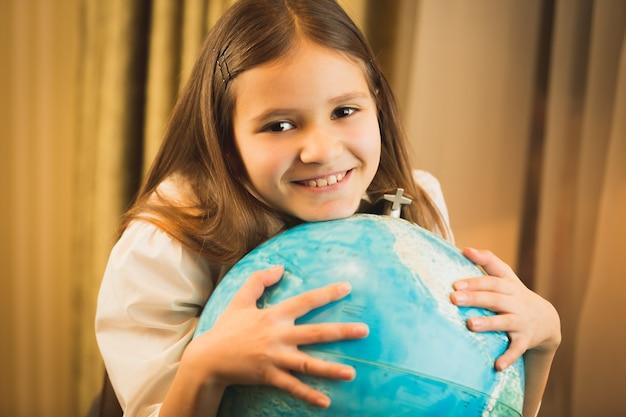 Porträt des netten mädchens, das hand auf globus hält
