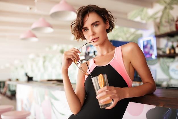 Porträt des netten mädchens im trendigen badeanzug, der sich auf die strandbar mit sonnenbrille und cocktail in den händen stützt. junge schöne dame, die am bartheke steht und nachdenklich schaut