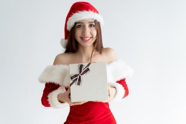 Porträt des netten mädchens in santa claus-kleid, das geschenkbox gibt