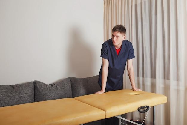 Porträt des netten masseurs des jungen mannes im blauen medizinischen hemd. masseur mit heimmassagegerät wartet auf kunden. konzept der individuellen massage, des service und des gesunden lebensstils. platz kopieren