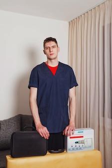 Porträt des netten masseurs des jungen mannes im blauen medizinischen hemd