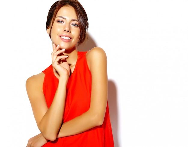 Porträt des netten modells der jungen frau der mode in einem roten kleid auf einer weißen wand