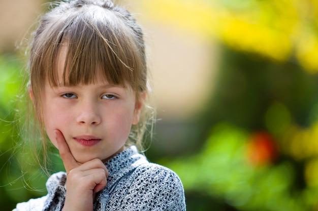 Porträt des netten recht durchdachten kindermädchens draußen auf unscharfem sonnigem buntem hellem.
