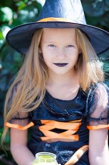 Porträt des netten tragenden hexenkostüms des kleinen mädchens mit besen auf halloween