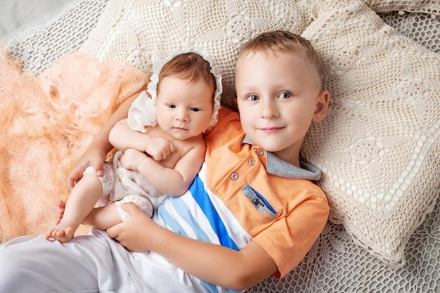 Porträt des neugeborenen mädchens und des älteren bruders. junge, der mit neugeborener schwester liegt