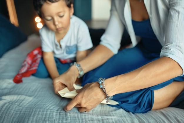 Porträt des neugierigen dunkelhäutigen kleinen jungen, der auf bett sitzt und seine mutter sieht, die origami macht