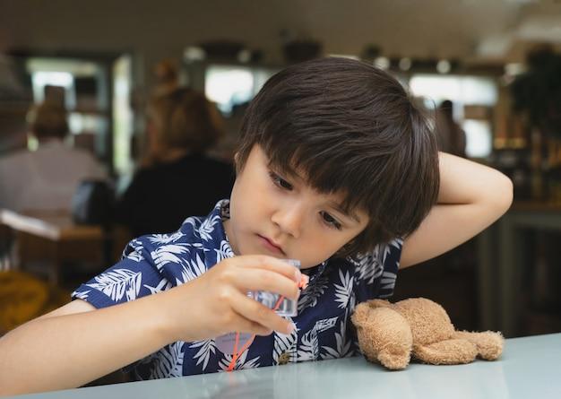 Porträt des neugierigen kindes, das plastikkäferkasten betrachtet und mit seinem spielzeug spielt, während er im café sitzt