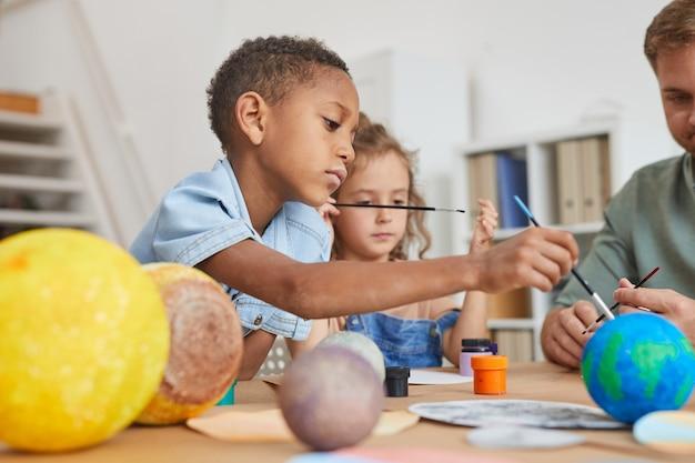 Porträt des niedlichen afroamerikanischen jungen, der planetenmodell malt, während kunst- und handwerksunterricht in der schule oder im entwicklungszentrum genießt