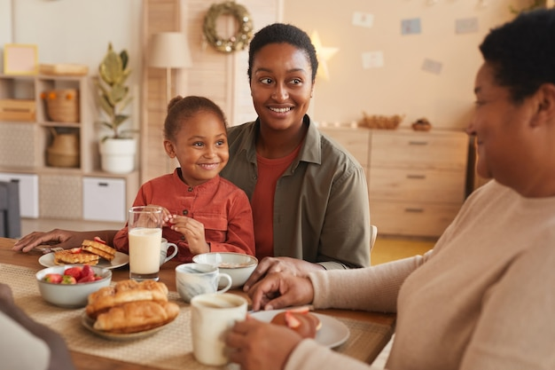 Porträt des niedlichen afroamerikanischen mädchens, das frühstück mit mutter und oma im gemütlichen innenraum genießt