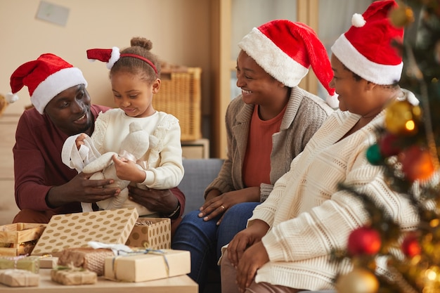 Porträt des niedlichen afroamerikanischen mädchens, das weihnachtsgeschenke mit familie öffnet, die alle weihnachtsmützen tragen, während ferienzeit zu hause genießen