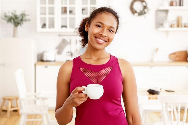Porträt des niedlichen afroamerikanischen mädchens mit gesammeltem haar, das im kücheninnenraum mit tasse tee aufwirft. attraktive glückliche dunkelhäutige frau, die kaffee mit zahnigem lächeln trinkt