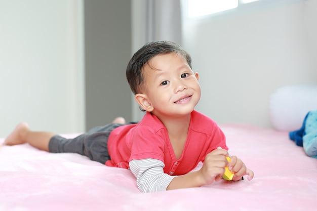 Porträt des niedlichen asiatischen kleinen jungen, der auf dem bett liegt