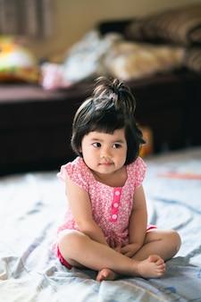 Porträt des niedlichen babys, das auf dem bett sitzt