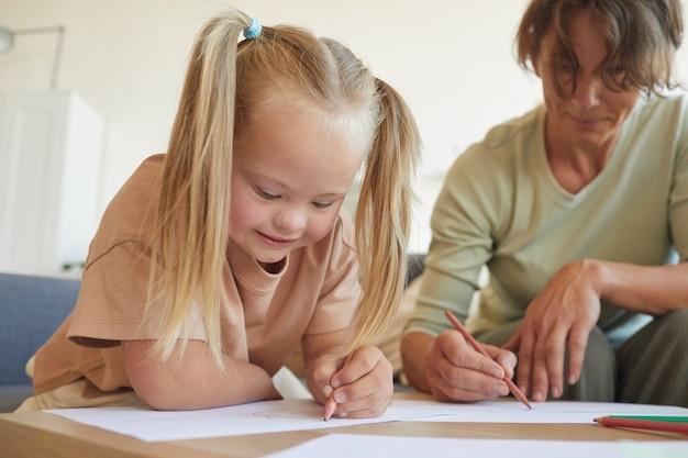 Porträt des niedlichen blonden mädchens mit down-syndrom-zeichnung mit mutter oder lehrer beim genießen von entwicklungsübungen