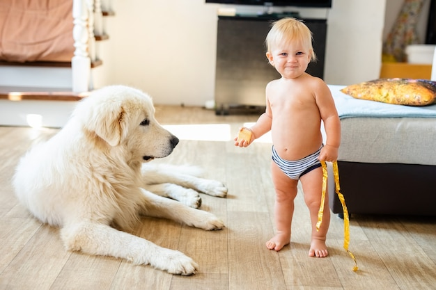 Porträt des niedlichen entzückenden kleinen blonden jungen, der mit hund zu hause sitzt.