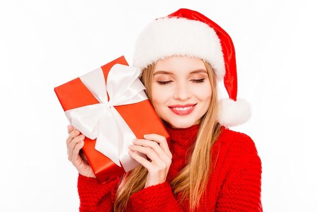 Porträt des niedlichen glücklichen mädchens, das kasten hält und vom weihnachtsgeschenk träumt