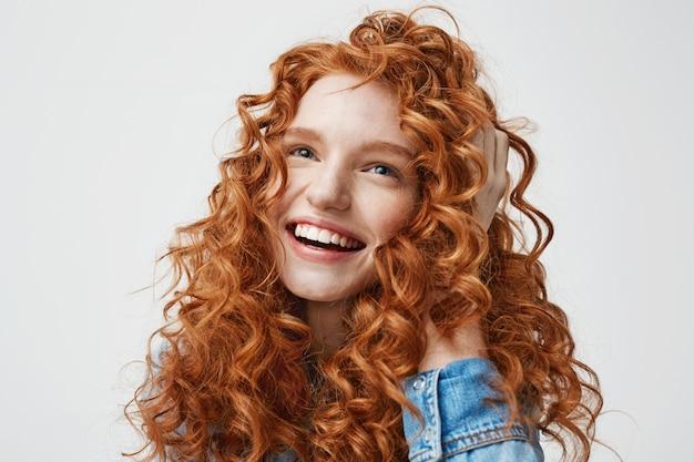 Porträt des niedlichen glücklichen mädchens lächelnd, das ihr lockiges rotes haar berührt.