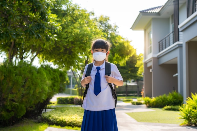 Porträt des niedlichen grundschulmädchens in der medizinischen maske vor zu hause
