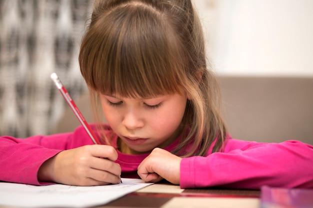Porträt des niedlichen hübschen kleinen ernsten kindermädchens, das mit bleistift auf papier zeichnet. kunstvermittlung, kreativität, hausaufgaben und kinderaktivitäten konzept.