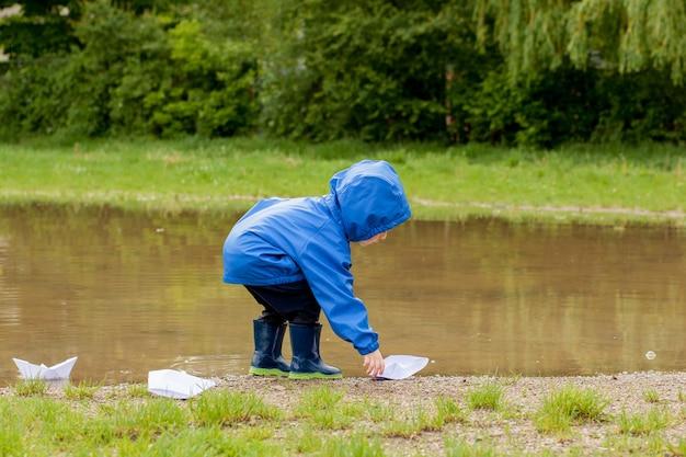 Porträt des niedlichen jungen, der mit handgemachtem schiff spielt. kindergartenjunge segelt ein spielzeugboot am wasser
