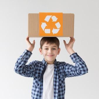 Porträt des niedlichen jungen, der mit recyclingbox aufwirft