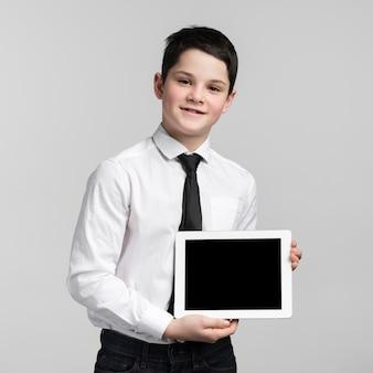 Porträt des niedlichen jungen, der tablette hält
