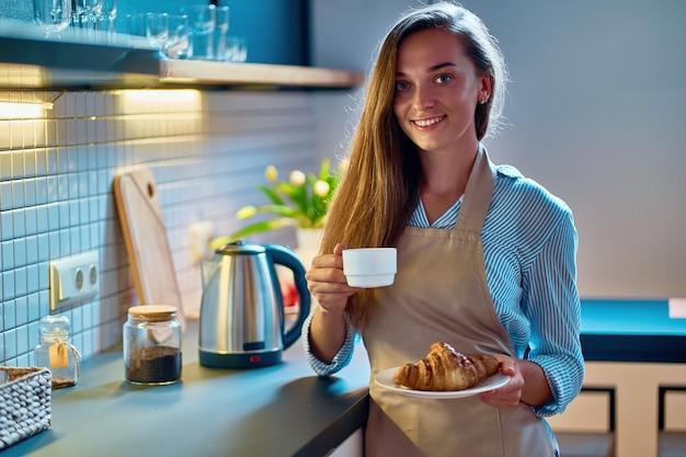 Porträt des niedlichen jungen glücklichen lächelnden frauenbäckers, der eine weiße tasse und teller croissant an der dachbodenküche hält