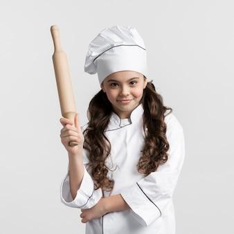 Porträt des niedlichen jungen kochs, der nudelholz hält