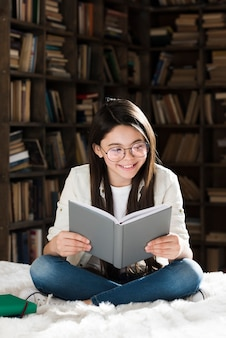 Porträt des niedlichen jungen mädchens, das ein buch liest