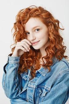 Porträt des niedlichen jungen mädchens mit rotem lockigem haar und sommersprossen lächelnd.
