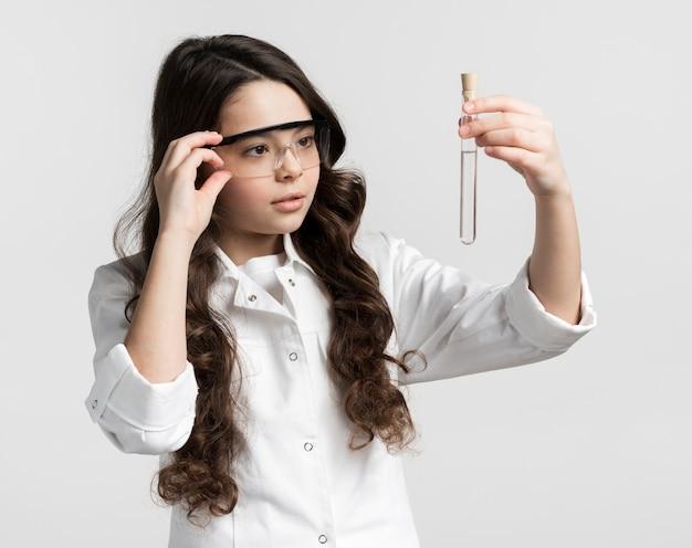 Porträt des niedlichen jungen wissenschaftlers, der chemieprobe prüft