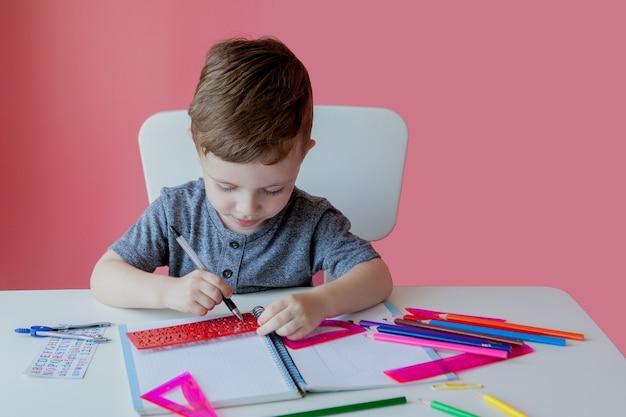 Porträt des niedlichen kinderjungen zu hause, der hausaufgaben macht. kleines konzentriertes kind, das mit buntem bleistift drinnen schreibt.