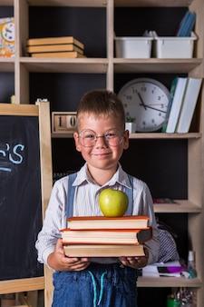 Porträt des niedlichen kleinen jungen, der buch im klassenzimmer hält. glücklicher internationaler tag der alphabetisierung.